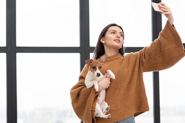 Mulher segurando o cachorro e tomar selfie