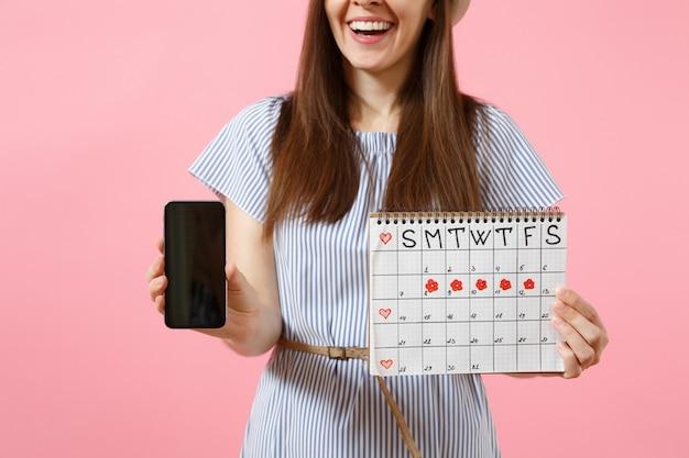 Mulher segurando o calendário de períodos femininos para verificar os dias de menstruação, celular com tela preta em branco vazia, isolada no fundo rosa. conceito médico, de saúde e ginecológico. copie o espaço.