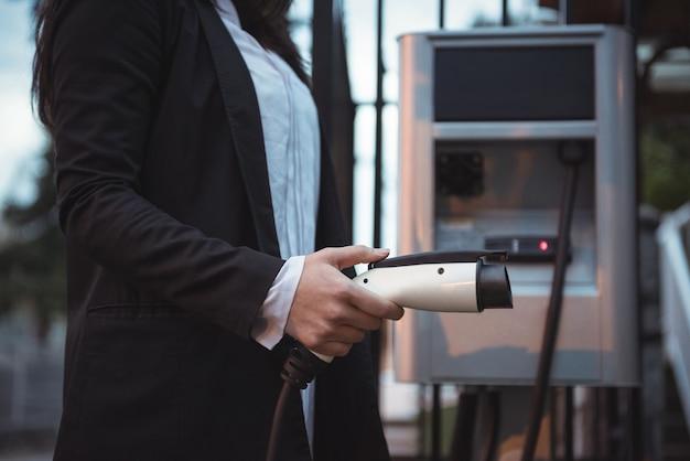 Mulher segurando o carregador do carro na estação de carregamento de veículos elétricos