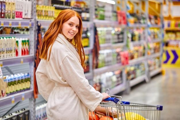 Mulher segurando o carrinho no supermercado, andando pelas prateleiras com comida no supermercado