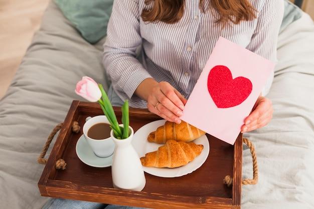 Mulher segurando o cartão com desenho de coração vermelho