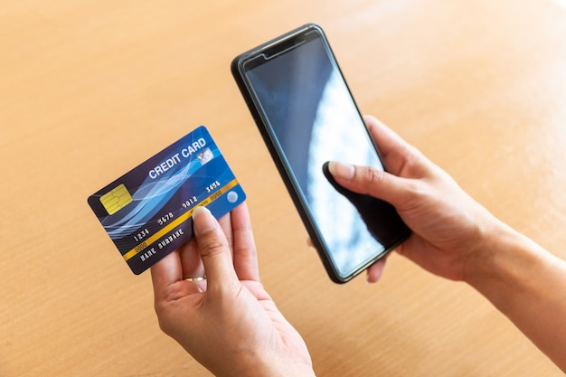 Mulher segurando o cartão de crédito e smartphone. compras on-line na internet usando um smartphone