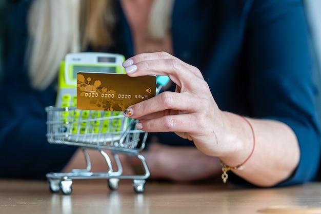 Mulher segurando o cartão de crédito na mão, mini carrinho de compras no fundo, conceito de pagamento não em dinheiro