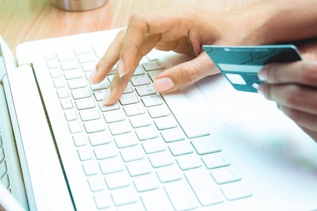 Mulher segurando o cartão de crédito no laptop. compras on-line, conceito de banca on-line