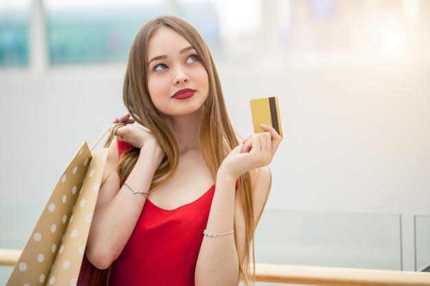 Mulher segurando o cartão de crédito, sacola de compras, no shopping shoping.