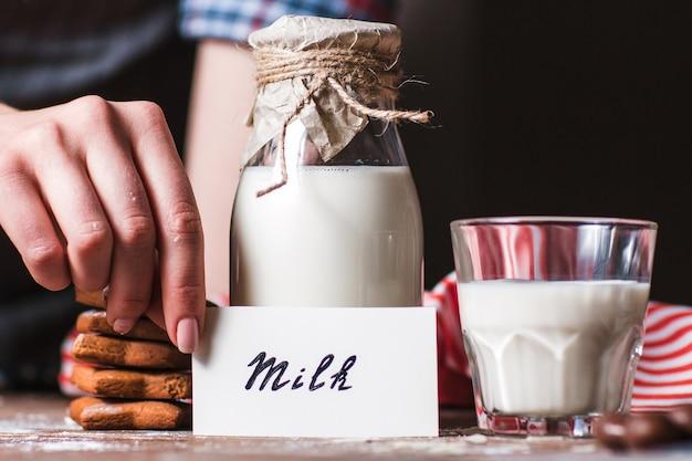 Mulher segurando o cartão perto da garrafa de leite.