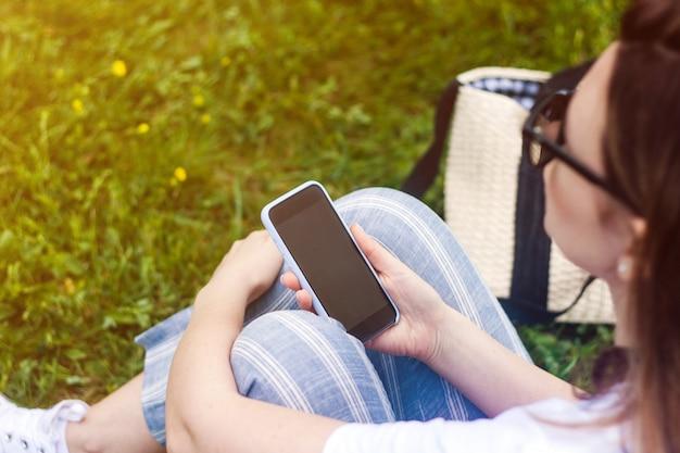 Mulher segurando o celular com tela escura na mão dela.