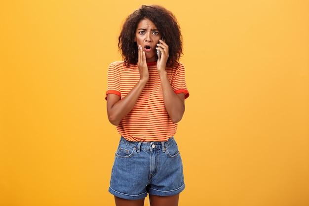 Mulher segurando o celular e tocando sua bochecha, sentindo-se triste.