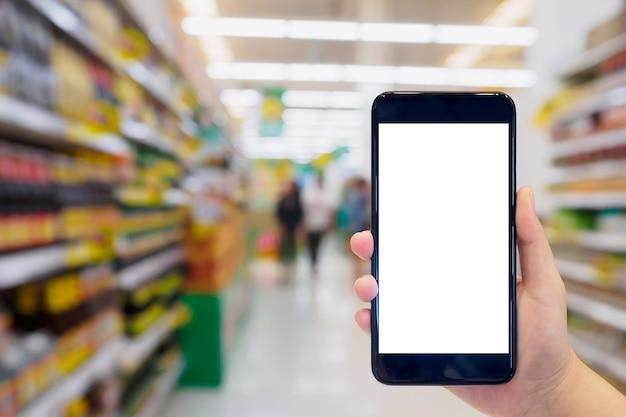 Mulher segurando o celular enquanto faz compras no supermercado