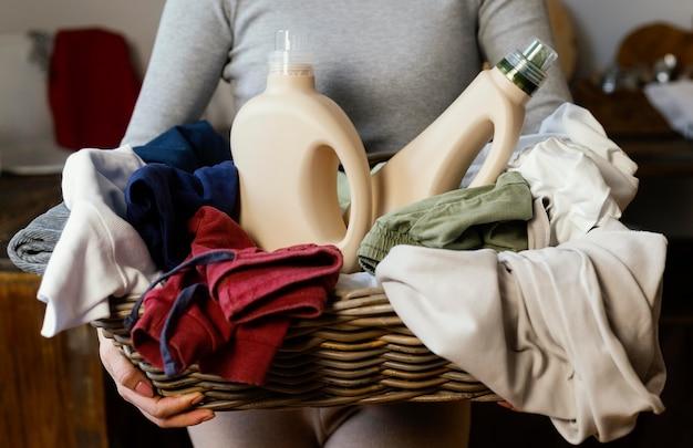 Mulher segurando o cesto de roupa suja de perto