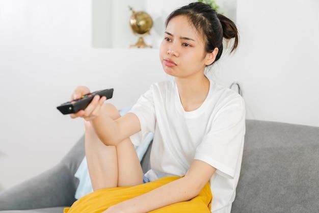 Mulher segurando o controle remoto da tv para assistir filmes.