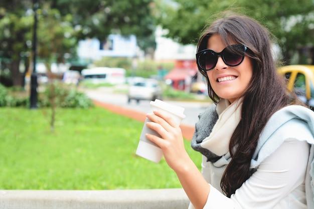 Mulher segurando o copo de café de papel na rua.