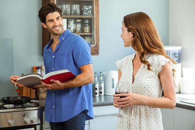 Mulher segurando o copo de vinho e homem cozinhando com livro de receitas