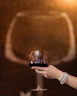 Mulher segurando o copo de vinho tinto com forma de vidro