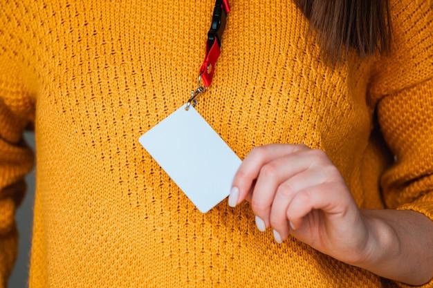 Mulher segurando o crachá com o nome do distintivo, com simulação de espaço em branco
