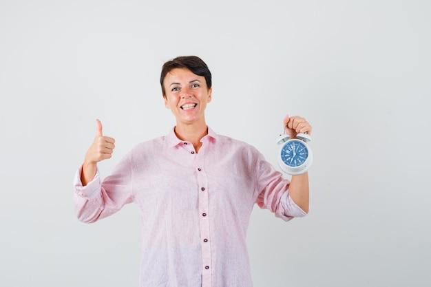 Mulher segurando o despertador, aparecendo o polegar na camisa rosa e olhando confiante, vista frontal.