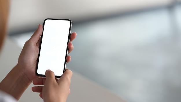 Mulher segurando o dispositivo móvel e tocando smartphone de tela em branco