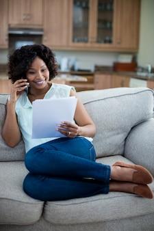 Mulher segurando o documento enquanto fala no celular na sala de estar