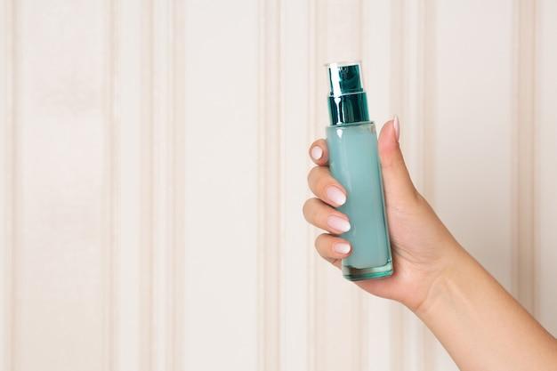 Mulher segurando o frasco de vidro com gel hidratante. espaço para texto