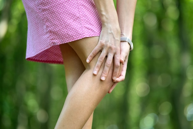 Mulher segurando o joelho com as mãos, tendo fortes dores.