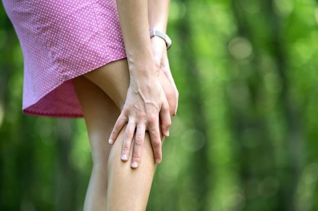 Mulher segurando o joelho com as mãos.