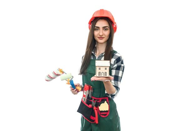 Mulher segurando o modelo da casa e o rolo isolado no branco