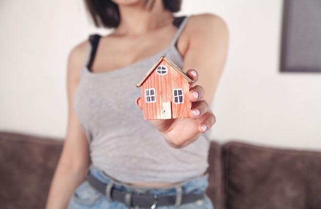 Mulher segurando o modelo da casa em casa.