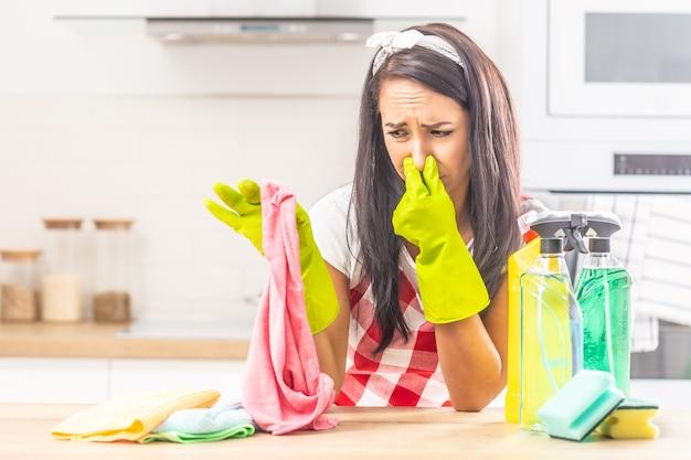 Mulher segurando o nariz com os dedos sobre um pano fedorento segurado na outra mão, encostada na mesa da cozinha, com material de limpeza em torno dela.