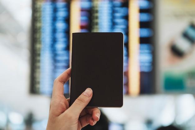 Mulher segurando o passaporte em frente a um painel de status de voo