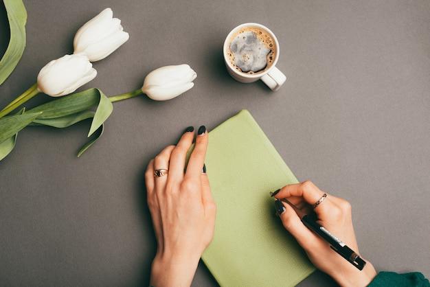 Mulher segurando o planejador ou a agenda perto de tulipas brancas e café da manhã