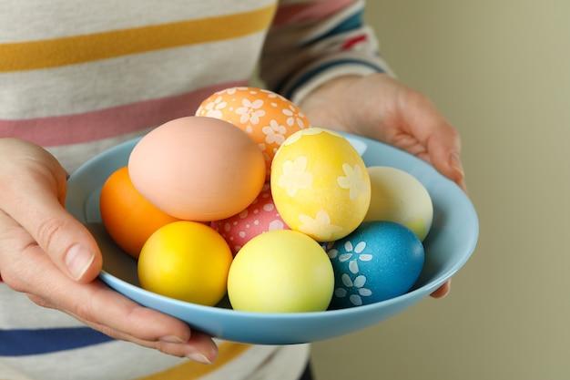 Mulher segurando o prato com ovos de páscoa, close-up