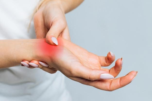 Mulher segurando o pulso doloroso causado por trabalho prolongado no computador. síndrome do túnel do carpo, artrite