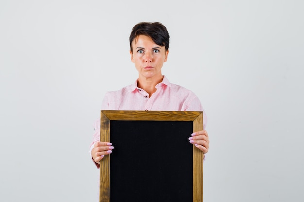 Mulher segurando o quadro-negro na camisa rosa e olhando sério. vista frontal.
