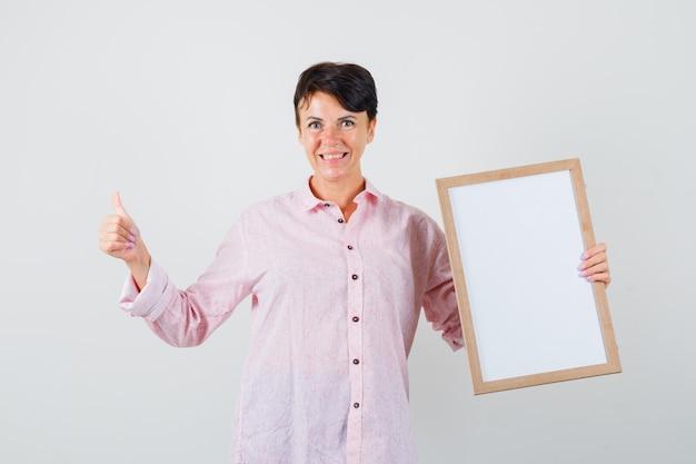 Mulher segurando o quadro vazio, aparecendo o polegar na camisa rosa e olhando alegre, vista frontal.