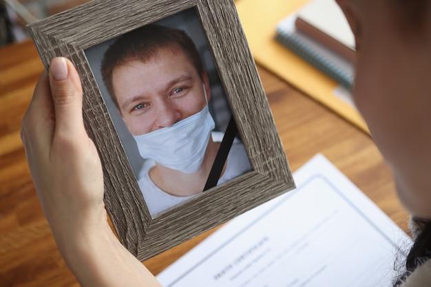 Mulher segurando o retrato do marido falecido com o uso impróprio de máscara médica protetora closeup