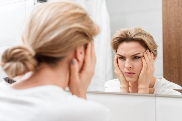 Mulher segurando o rosto dela e olhando no espelho