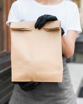 Mulher segurando o saco de entrega de comida