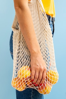 Mulher segurando o saco de malha branca com maçãs