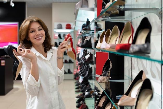 Mulher segurando o sapato de salto preto e sapato de salto vermelho na loja