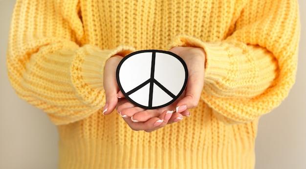 Mulher segurando o símbolo da paz de papel. conceito de liberdade, amor e paz