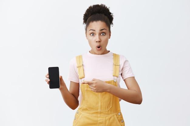 Mulher segurando o smartphone e apontando para a tela com o dedo indicador, dobrando os lábios de interesse e surpresa, em pé, chocada e impressionada