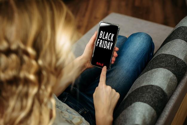 Mulher segurando o smartphone na mão, deitada no sofá. compras seguras em casa durante a quarentena.