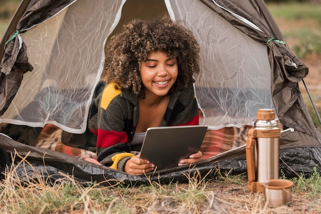 Mulher segurando o tablet dentro da barraca enquanto acampa