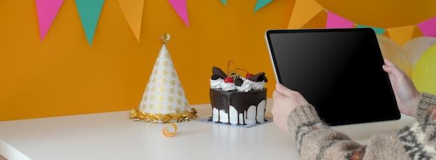 Mulher segurando o tablet digital enquanto está sentado na mesa