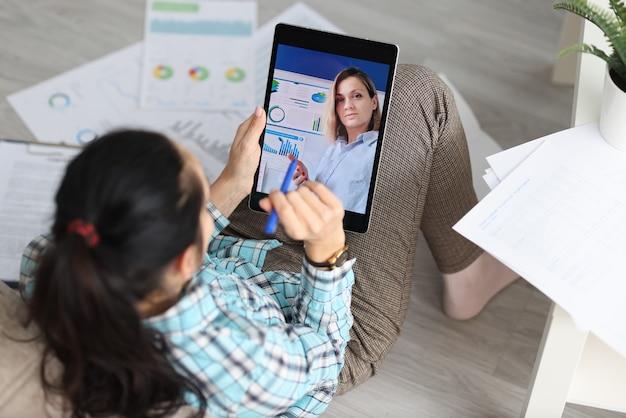 Mulher segurando o tablet e conversando com um colega de trabalho em casa. trabalho remoto durante um conceito de pandemia