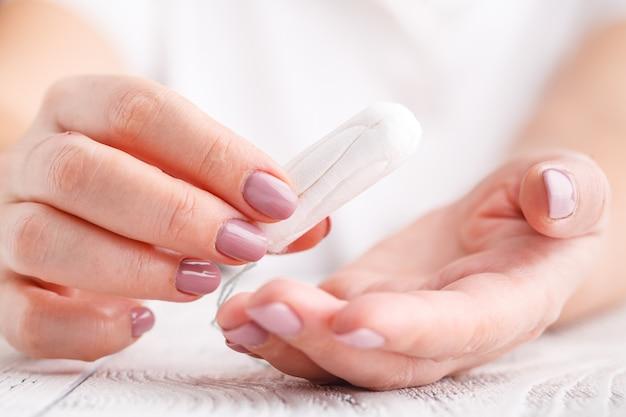 Mulher segurando o tampão menstrual em um fundo rosa. tempo de menstruação. higiene e proteção