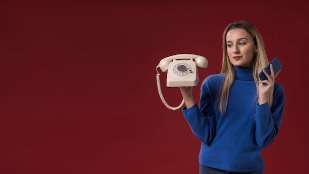 Mulher segurando o telefone antigo e novo