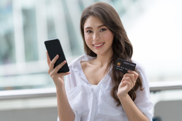 Mulher segurando o telefone com cartão de crédito e sorrindo perto da loja durante o processo de compra