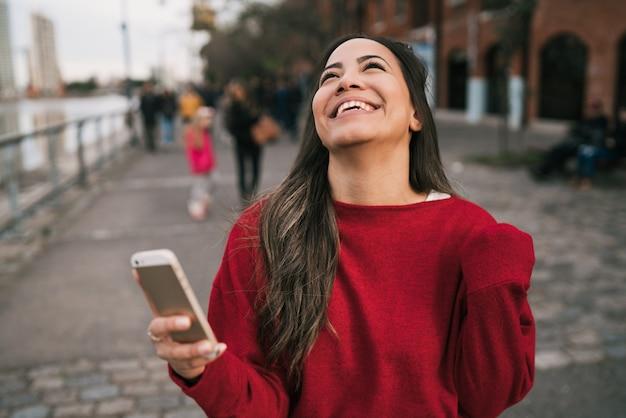 Mulher segurando o telefone com expressão de sucesso.
