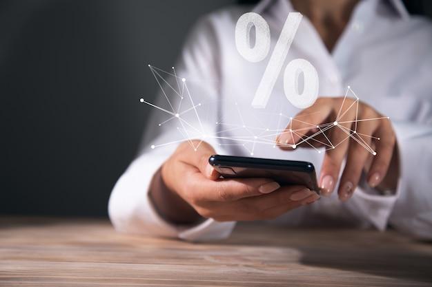 Mulher segurando o telefone com o ícone de venda ou porcentagem